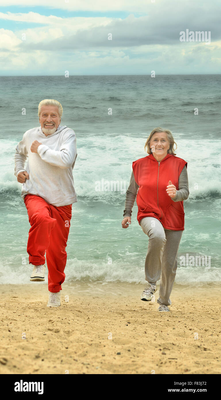 elderly couple running  on beach - Stock Image