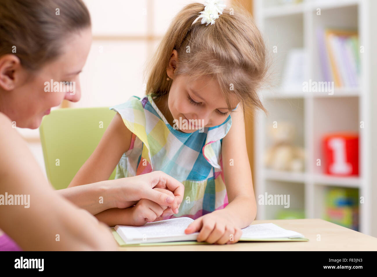 Preschooler Child Reading with Mother In Nursery at Home - Stock Image
