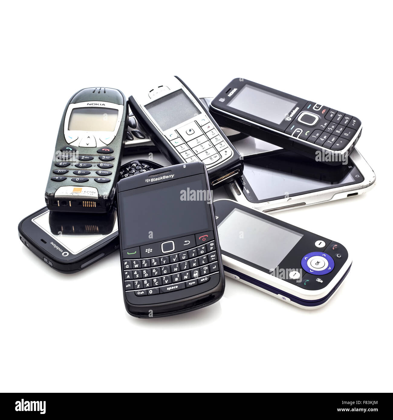 A Collection Of Old Mobile Cell Phones on A White Background - Stock Image