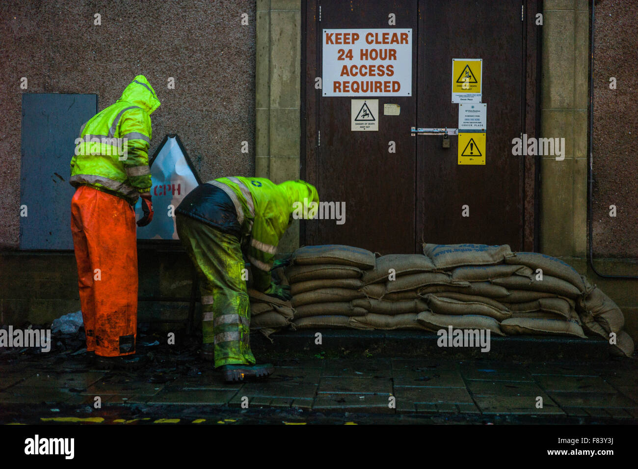 Hawick, Scotland, UK. 5th December 2015. Scottish Power workmen build sand bag barriers at sub stations in Hawick - Stock Image