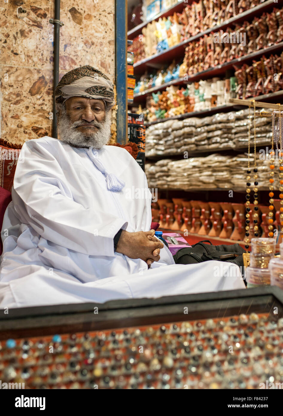 Omani man sitting outside his store in the Mutrah souk in Muscat, the capital of the Sultanate of Oman. - Stock Image