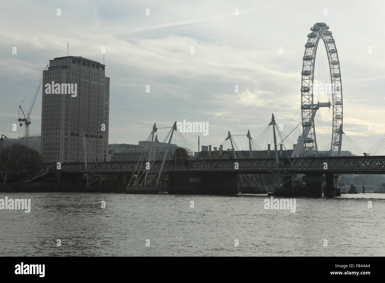 The Golden Jubilee Bridges cross the River Thames in London, UK. The London Eye rotates to the right of the image. - Stock Image