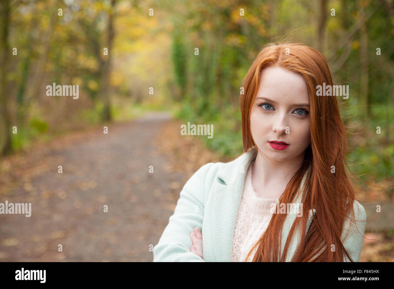 Redheaded woman outside with a forest path in the background. - Stock Image