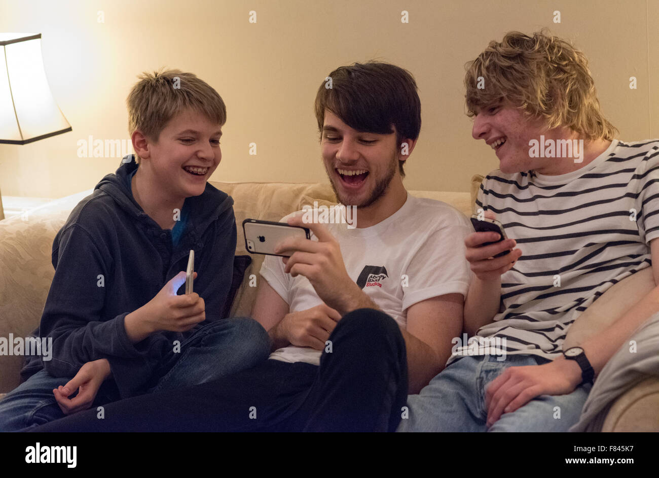 Three good-looking white happy teenage boys laughing and looking at their mobile phones playing online games, watching - Stock Image