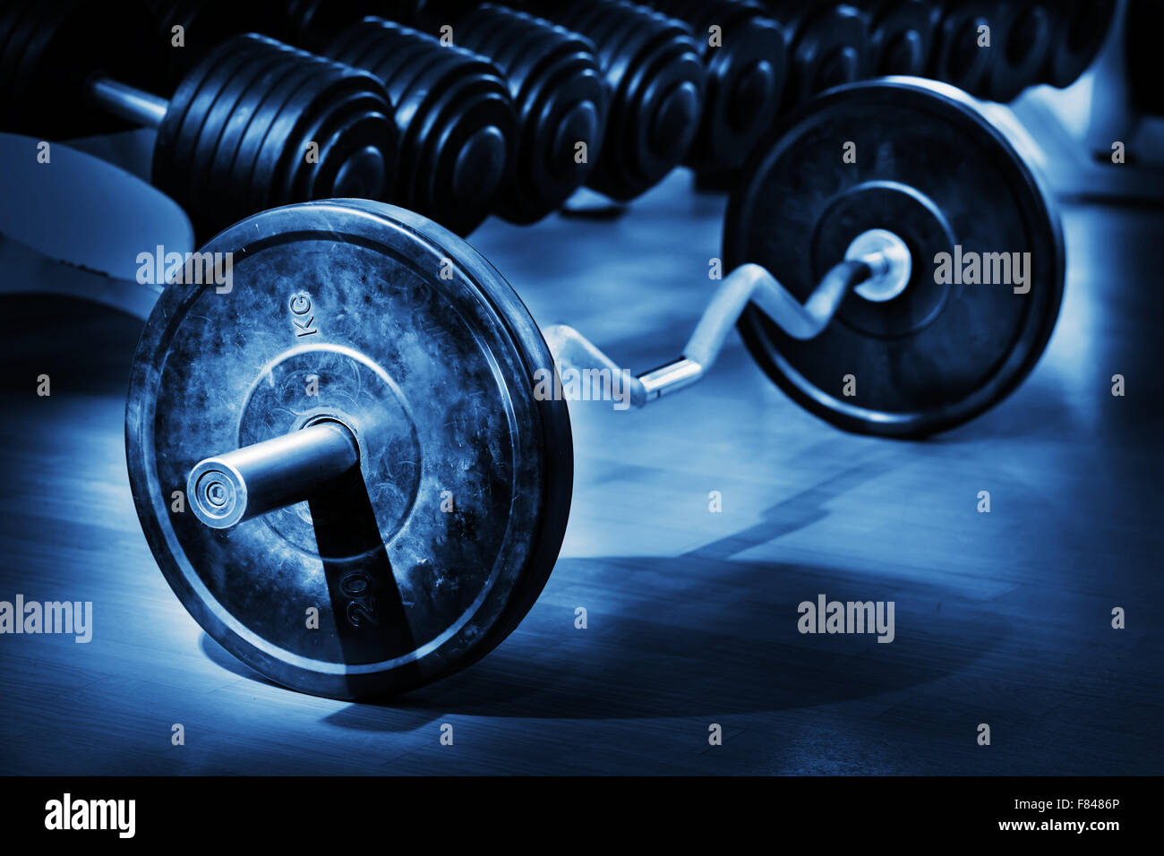 Barbell on the floor in gym lit fragmentary - Stock Image