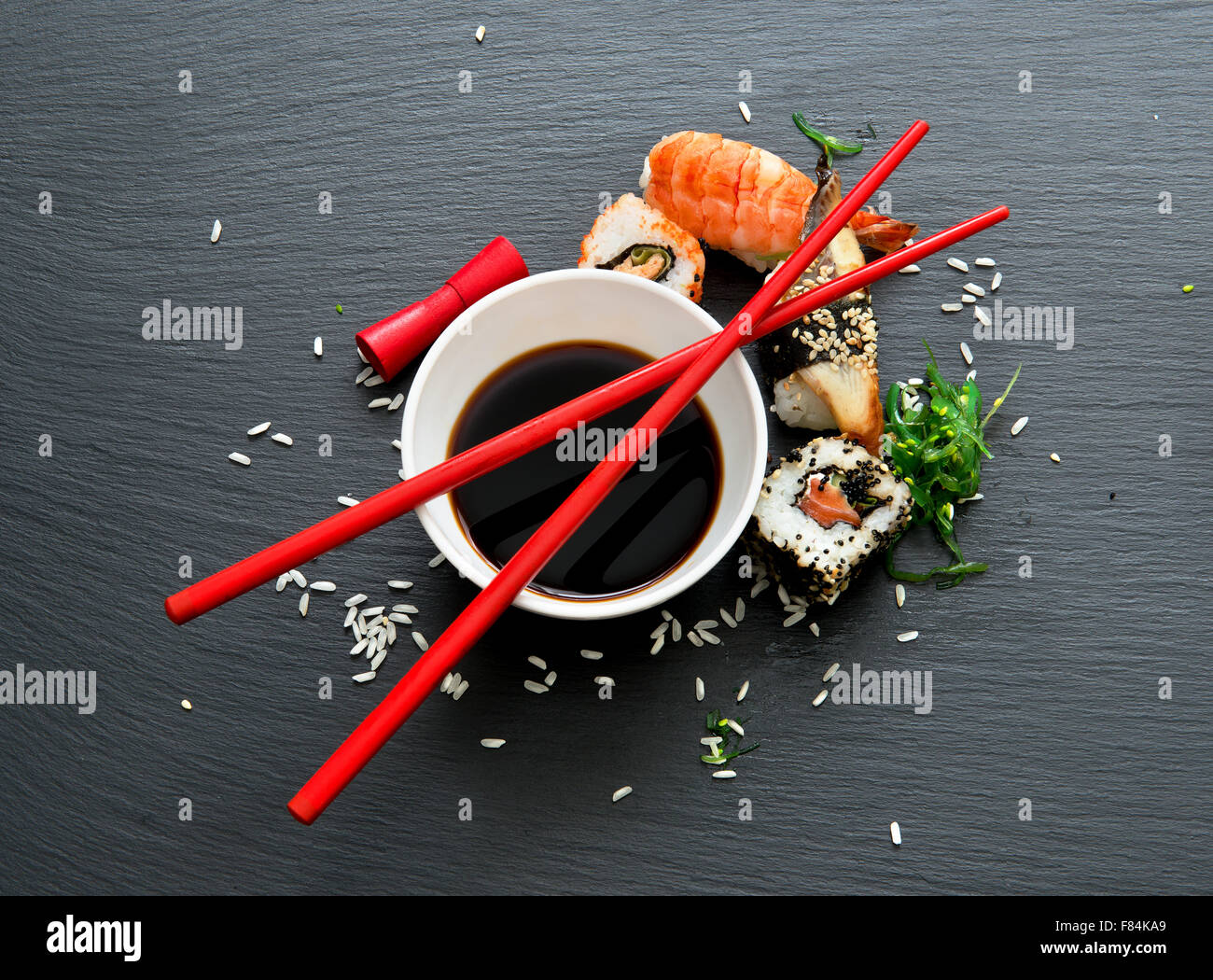 Sushi with soy in saucers on a slate table - Stock Image