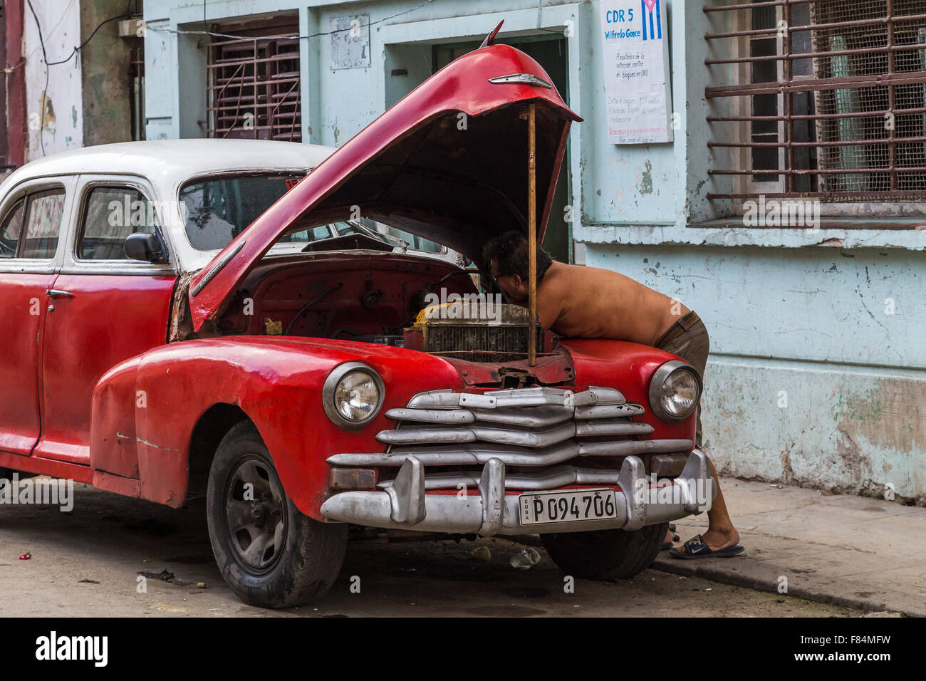 A man getting under the bonnet of his old timer in Centro Havana. - Stock Image