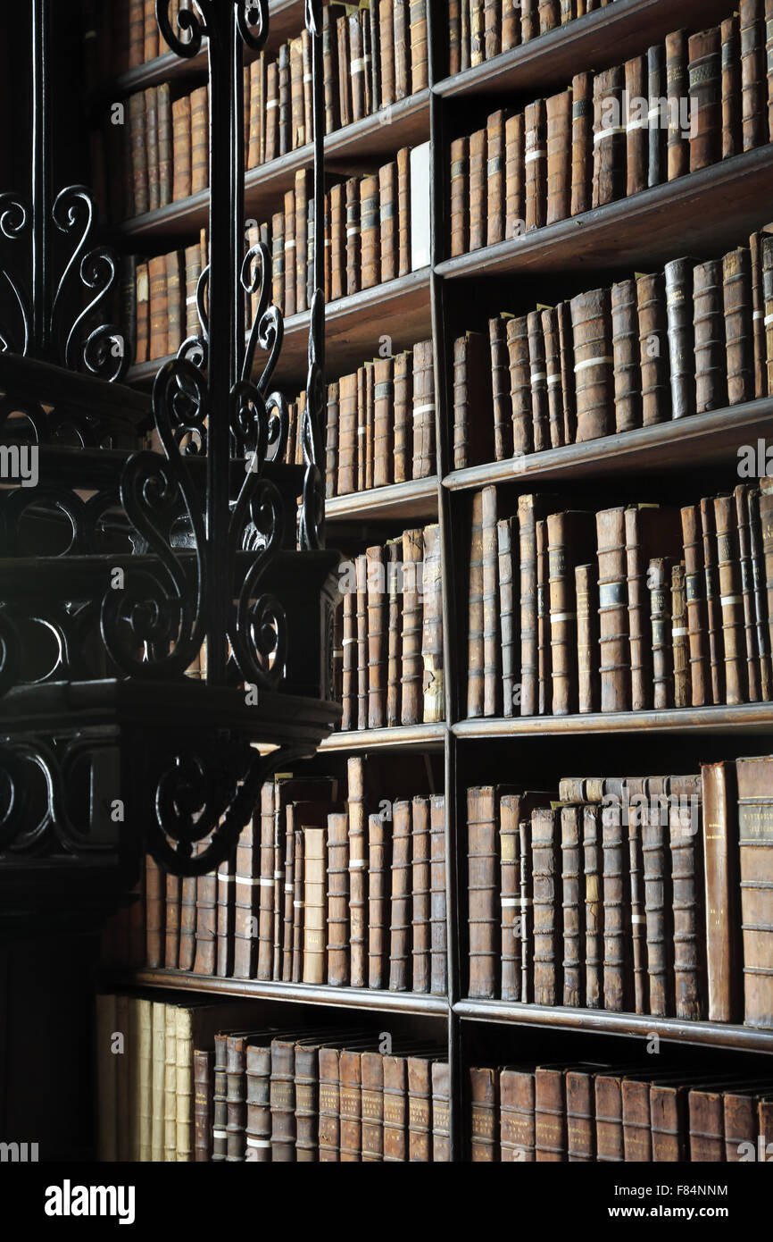 Antique books stored on the bookshelves inside of the Long Room of the Old Library of Trinity College in Dublin, - Stock Image