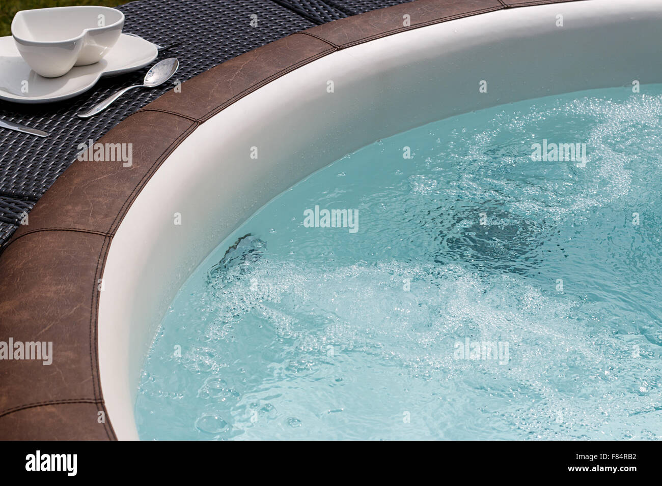 Luxurious standalone hot tub or jacuzzi with hot bubbling water Stock Photo