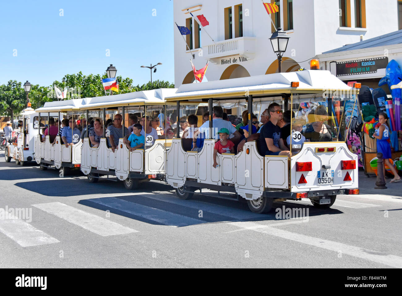 Sightseeing road train transport for visitors Saintes Maries de la Mer seaside resort town on Mediterranean coast - Stock Image