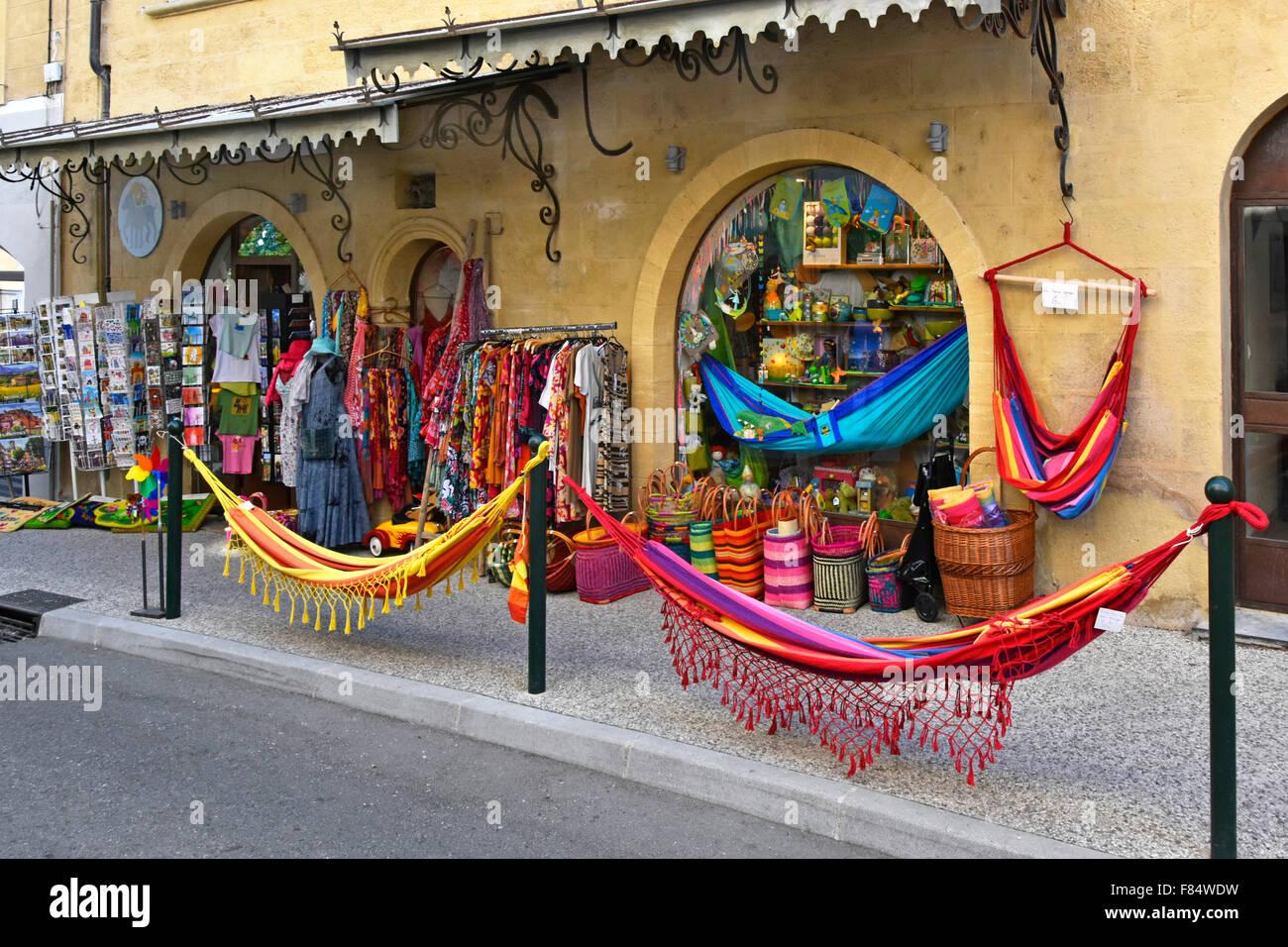 Lourmarin village street shop front pavement display of touristy summer merchandise including hammocks in Luberon, - Stock Image