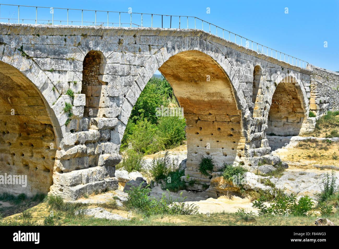 Roman Bridge French historic ancient monument stone arch bridge Pont Julien The Julien Bridge crossing the dried - Stock Image