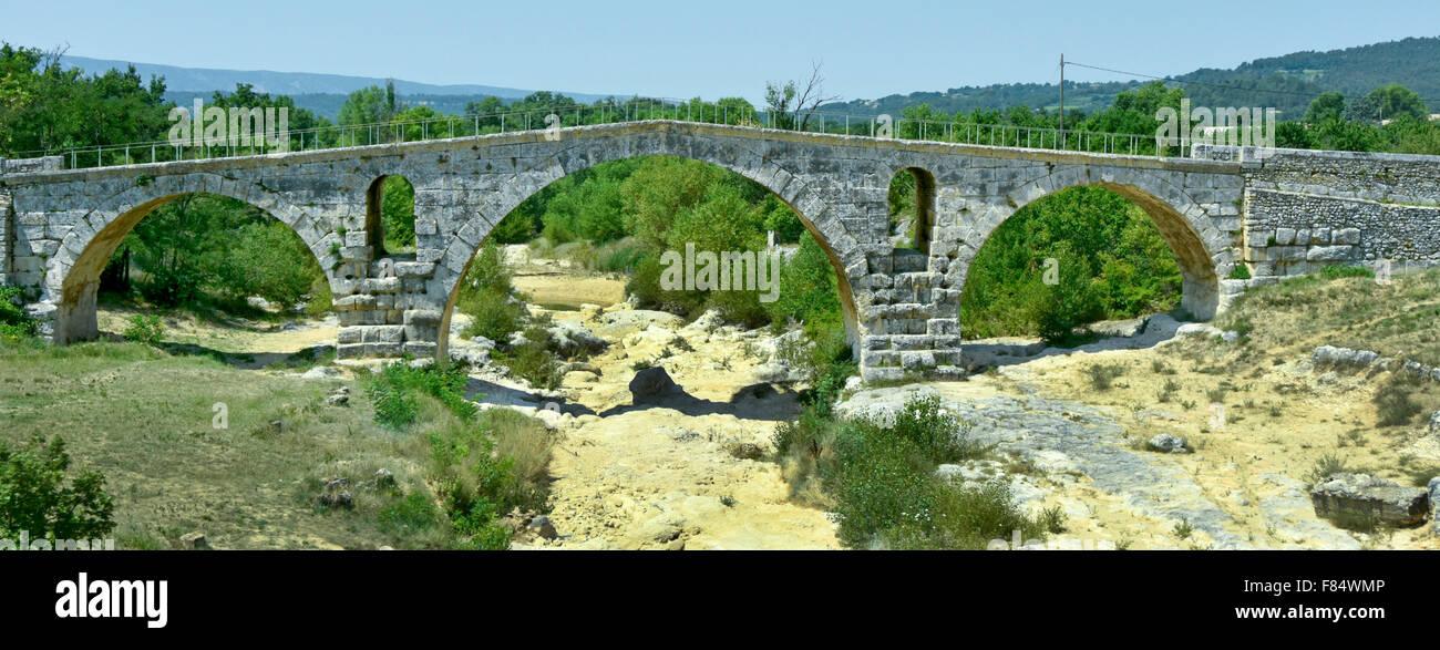 French historic monument the Roman stone arch bridge Pont Julien The Julien Bridge crossing the dried up Calavon - Stock Image