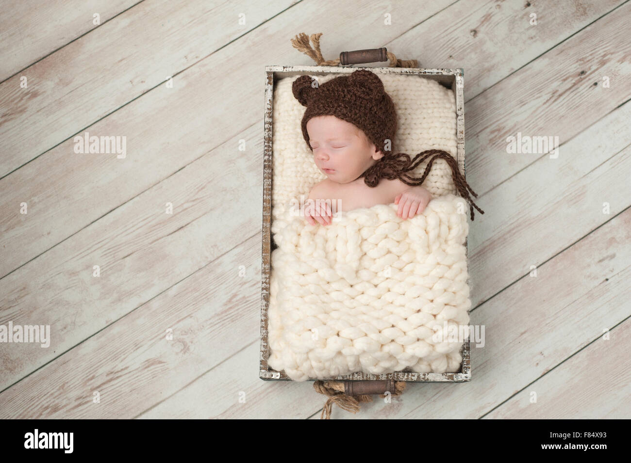 Two week old newborn baby boy wearing a brown, crocheted, bear bonnet. He  is sleeping in a rustic wooden crate. Shot in the stud f8a4d382987