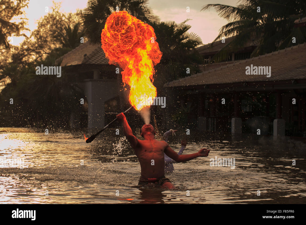 A Fire Breather in a pool in Thailand - Stock Image