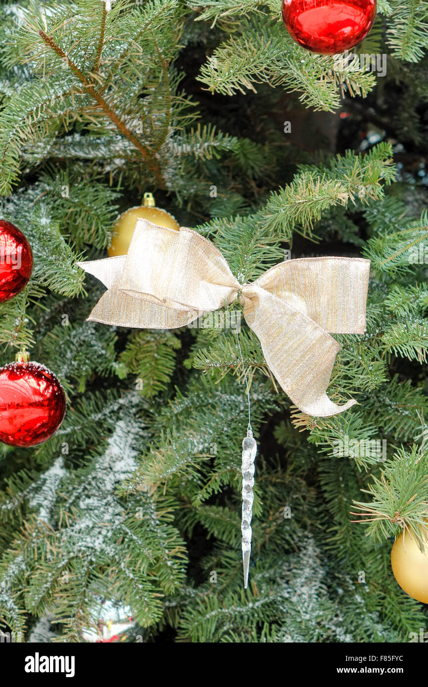close up of gold colored ribbon in center hanging in christmas tree with several