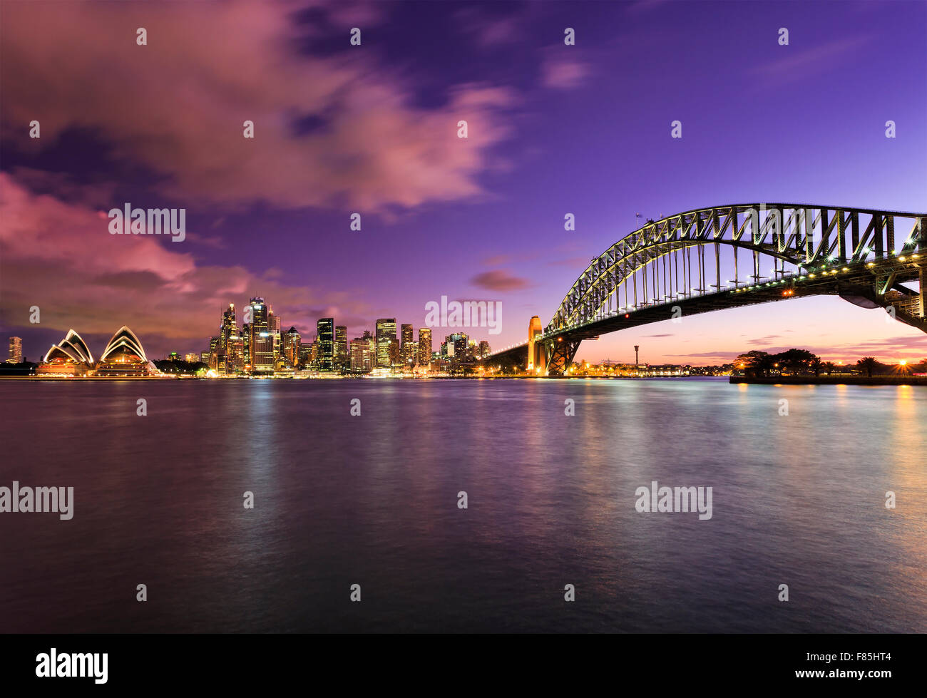 main Sydney landmarks at sunset across harbour with blurred clouds and water reflecting bright lights of colourful - Stock Image