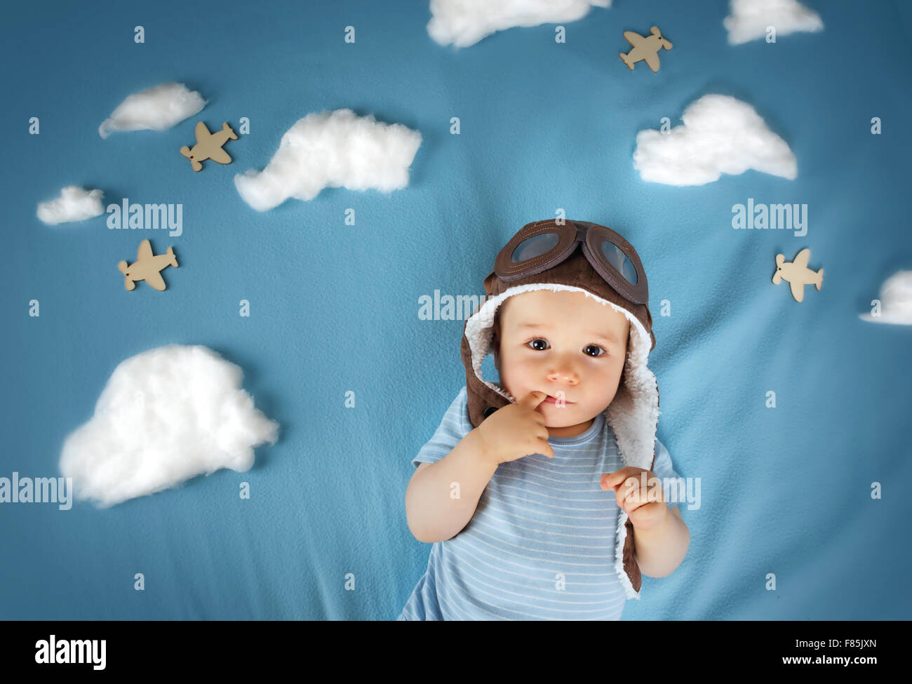 boy lying on blanket with white clouds - Stock Image
