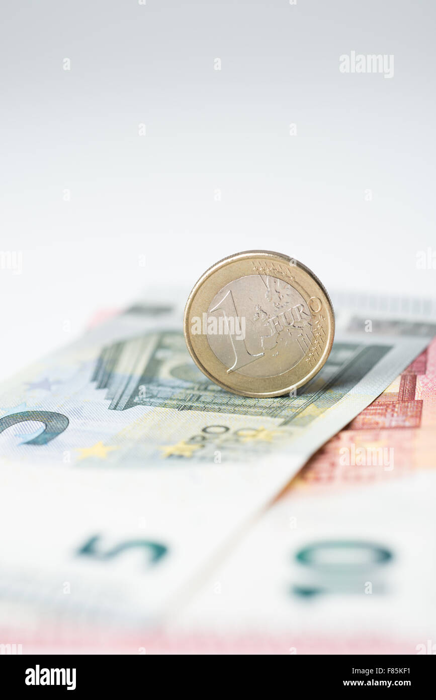 Five and ten euro note with euro coin - Stock Image
