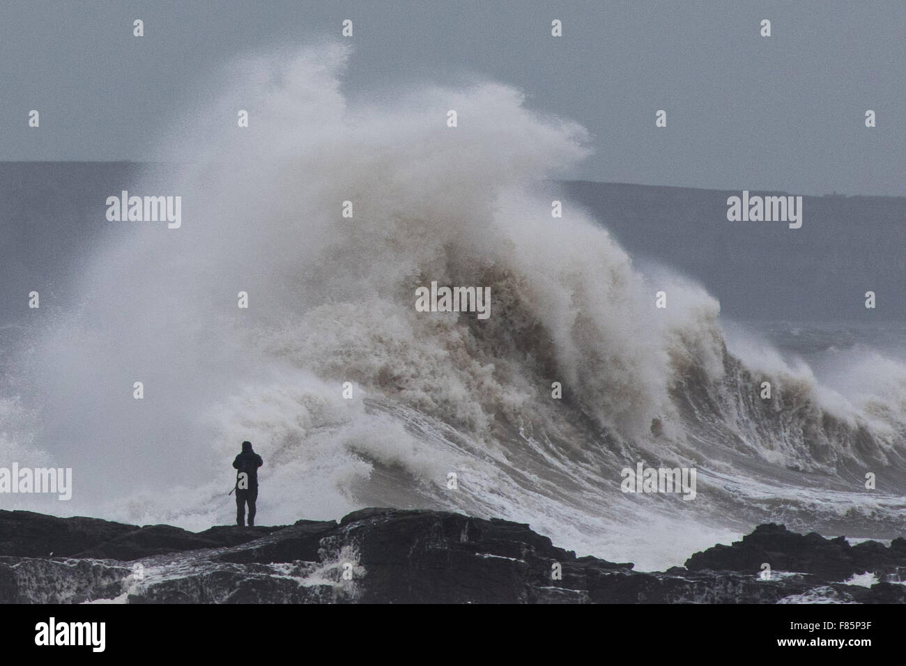 Porthcawl, Wales, UK. 5th December 2015. A photographer stands dangerously close to the sea in Porthcawl, as huge - Stock Image