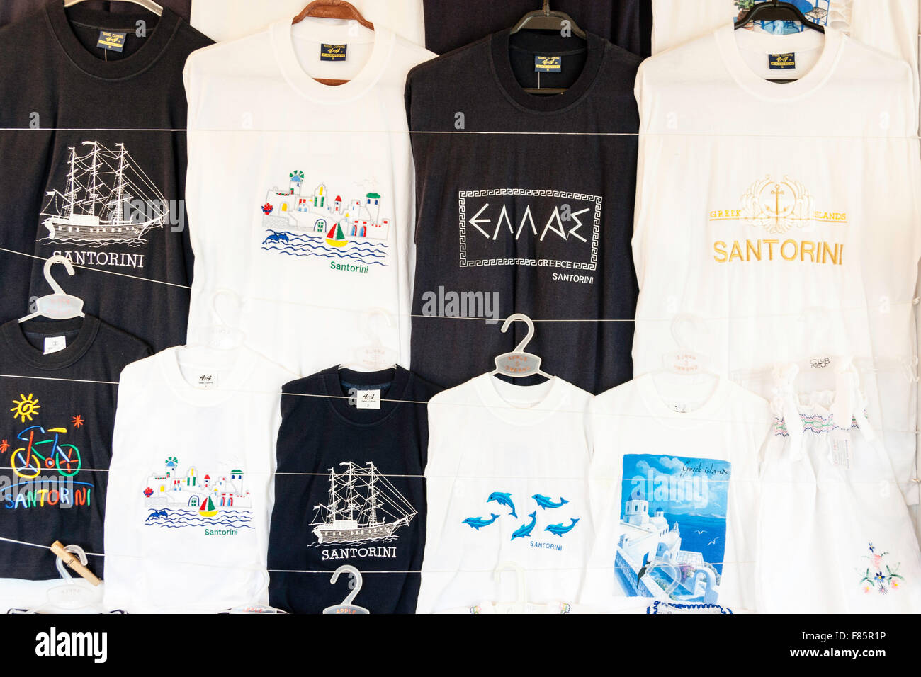 Santorini. Close up of hanging mainly black and white Greek and Santorini tee-shirts on display for sale outside - Stock Image