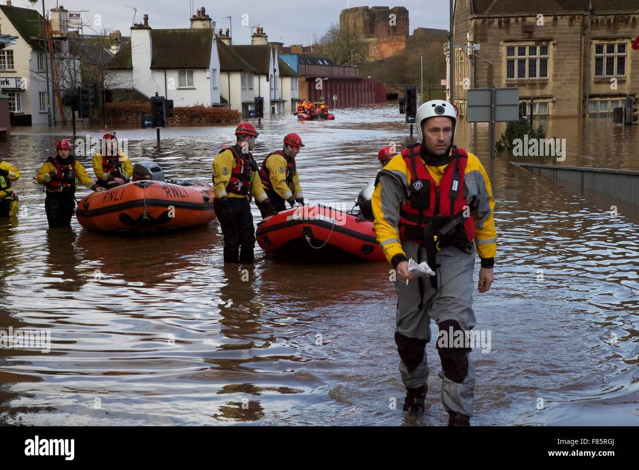 Cumbria Floods. 6th December 2015. RNLI rescue team volunteer wading through Carlisle city centre. Boats deployed - Stock Image
