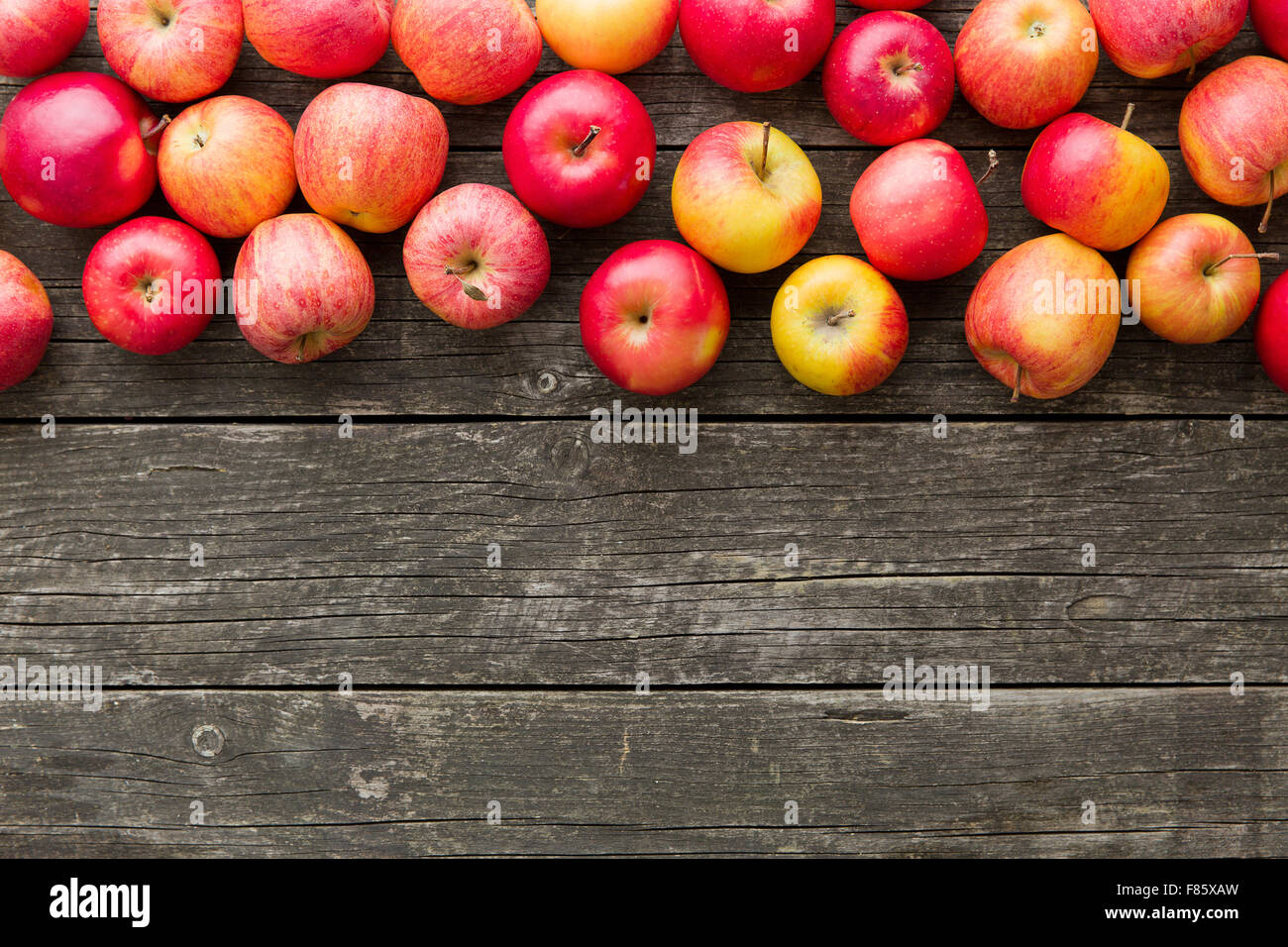 red autumn apples on old wooden table - Stock Image