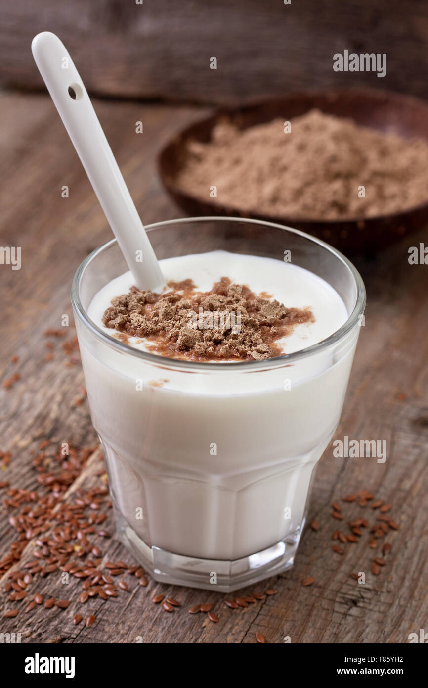 Glass of  yogurt with crushed flax seeds, flax flour in a wooden bowl  on a wooden background - Stock Image