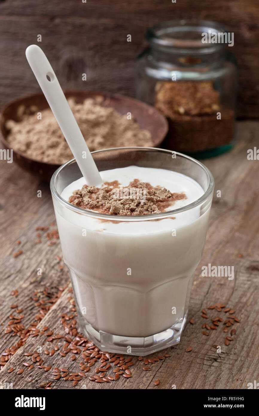 Glass of  yogurt with crushed flax seeds on a wooden background - Stock Image