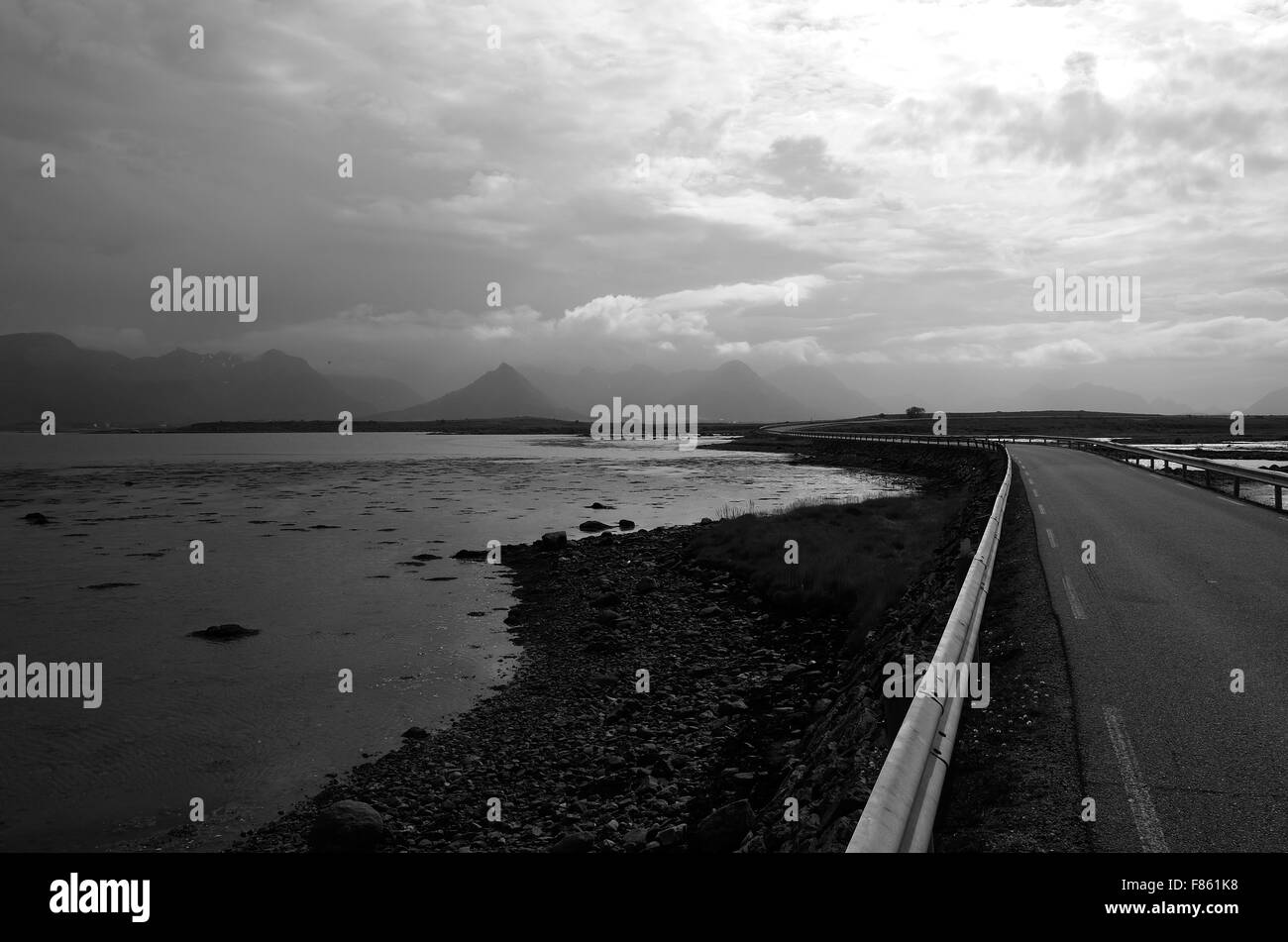 long road through flat landscape with mountain in background and ocean on sides - Stock Image