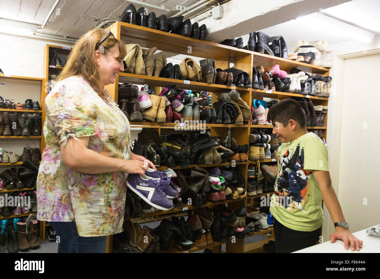 A volunteer shows donated shoes to a refugee boy. Shelves with donated shoes. Supporters of relief organisation - Stock Image