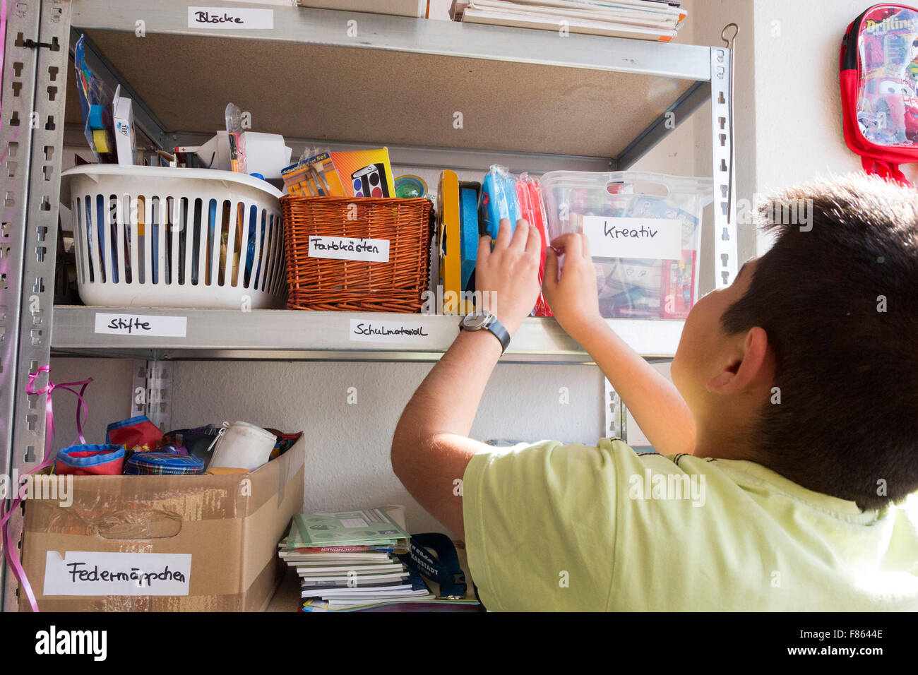 A refugee boy looks at toys on a shelf. Supporters of relief organisation Willkommen in Mülheim celebrate the - Stock Image