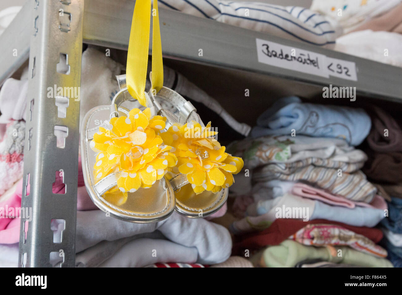 Donated children's clothing and shoes. Supporters of relief organisation Willkommen in Mülheim celebrate - Stock Image