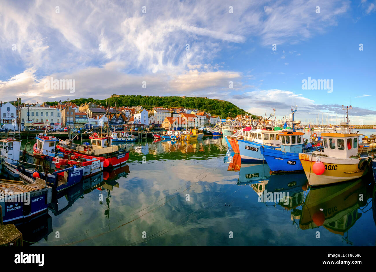 sunset at Scarborough harbor with boats and views to Scarborough castle - Stock Image