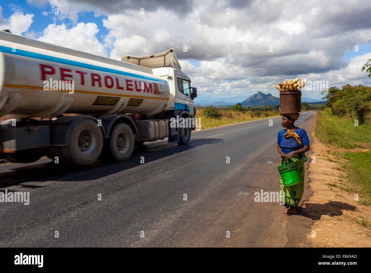 A poor Tanzanian woman carrying her meager produce to the local market when a passing petrol lorry epitomizes the - Stock Image