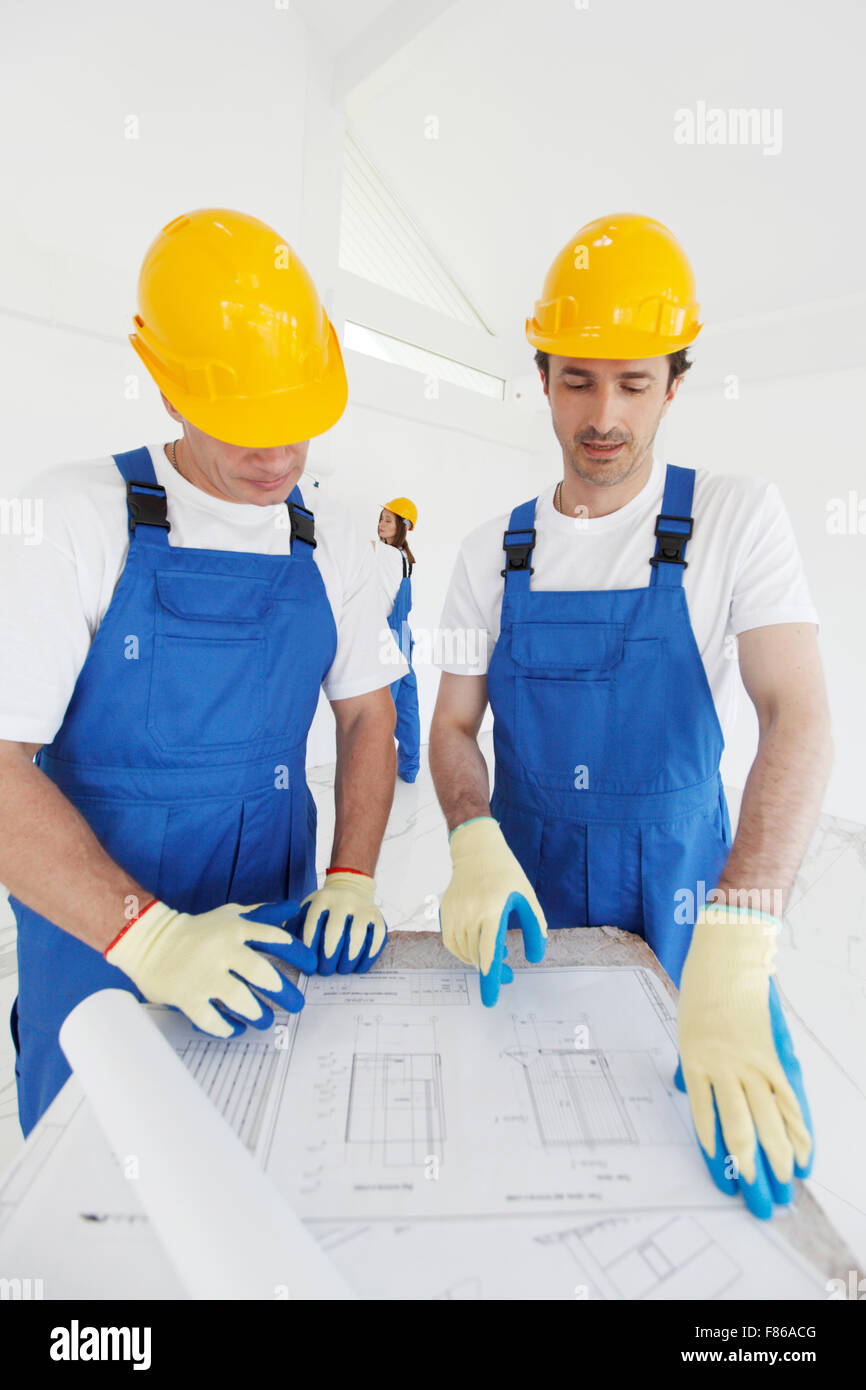 Workers looking at construction plan indoors - Stock Image