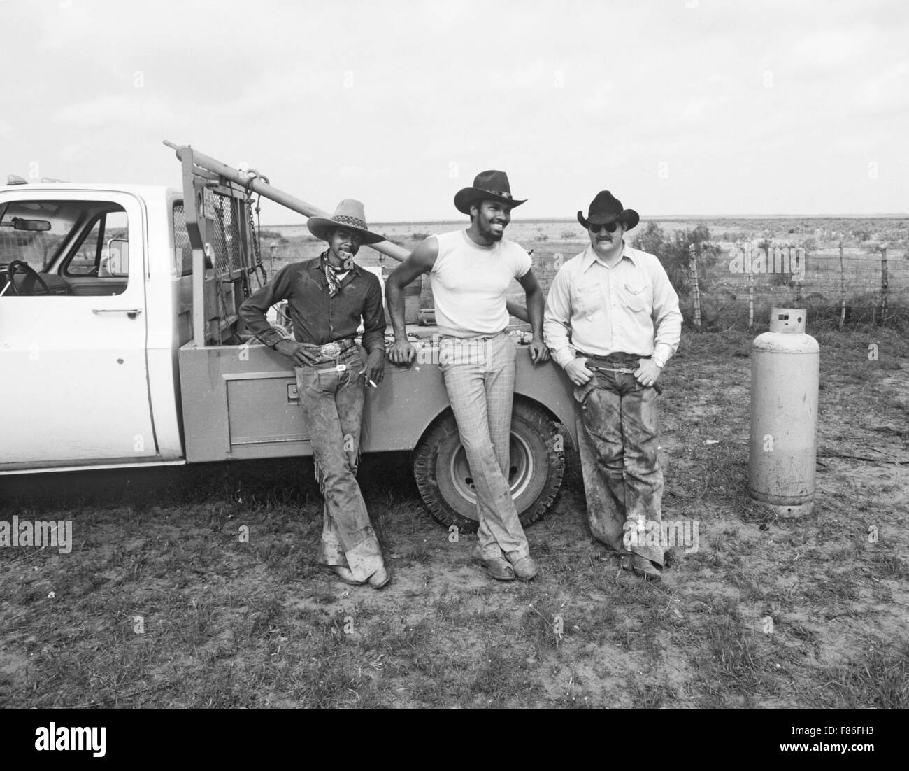 Ranch cowboys on the Macy Ranch in west Texas take a cigarette break during the  branding of calves. - Stock Image