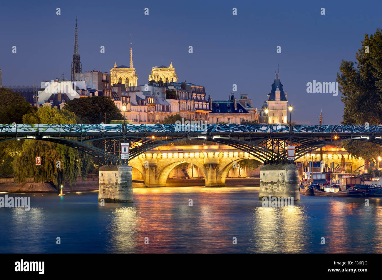 Pont des Arts, Pont Neuf, Notre Dame de Paris Cathedral towers and Seine River. Illuminated evening view. Ile de Stock Photo