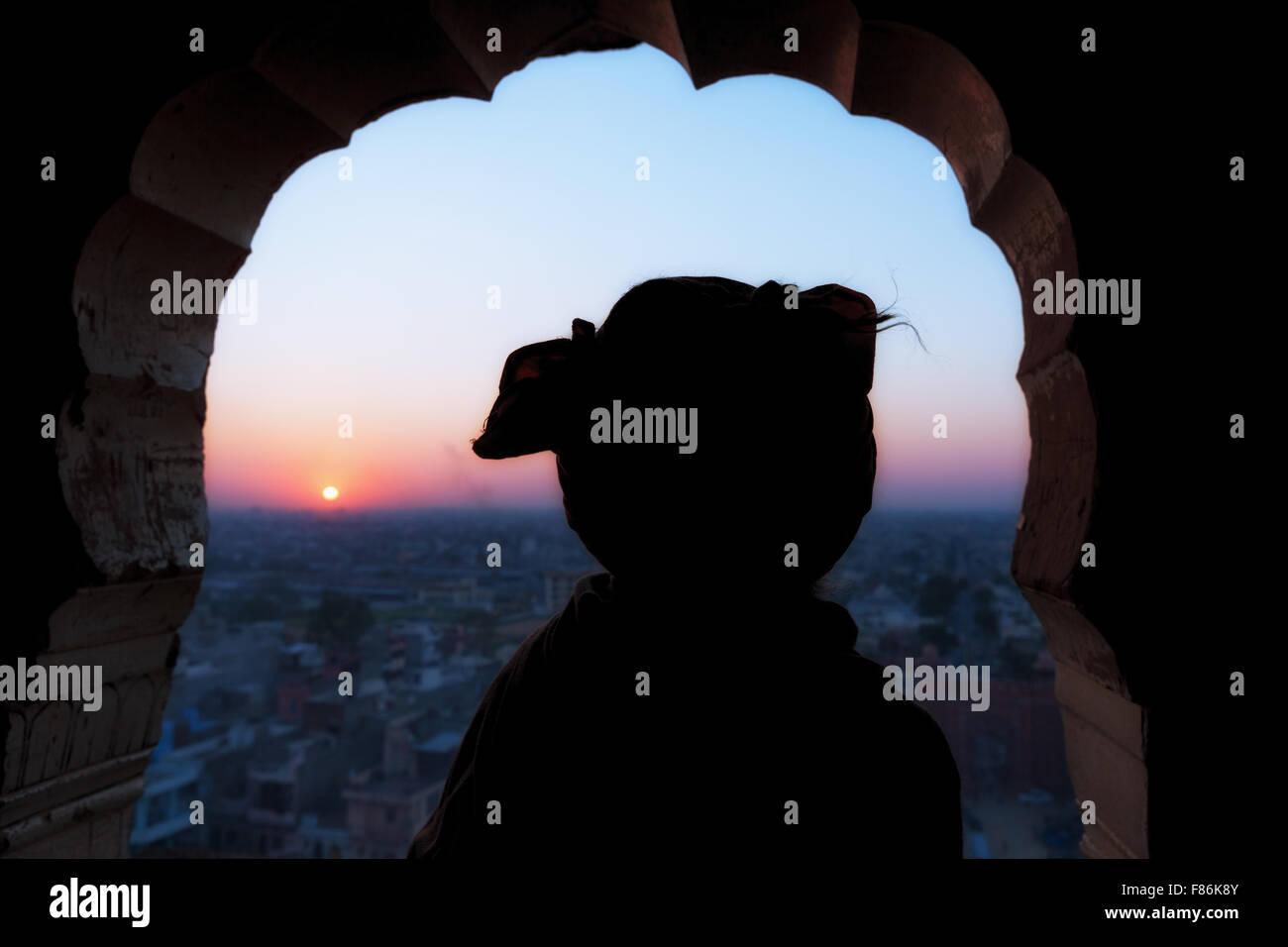 Silhouette of a Sadhu watching the sunset over Jaipur,  Galtaji, Khania-Balaji, Jaipur, Rajasthan, India - Stock Image