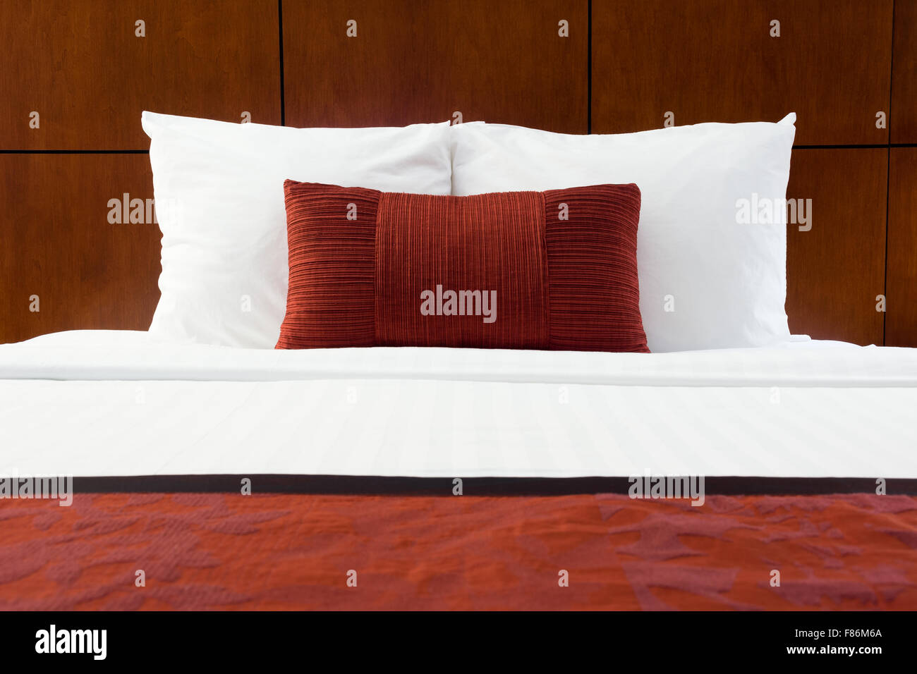 Hotel room bed, red pillows, and wood headboard at an upscale hotel - Stock Image