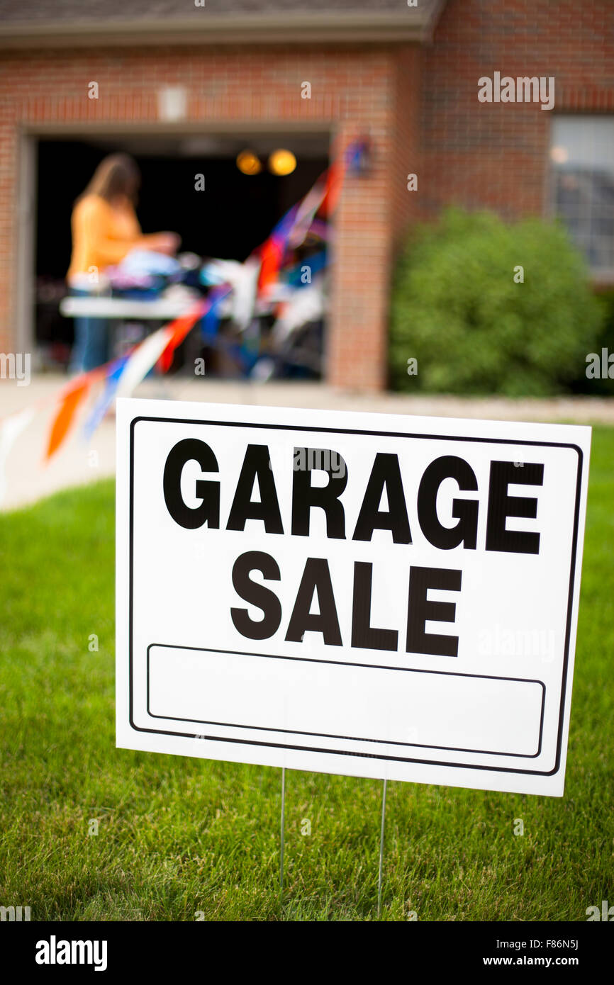 Garage sale sign on the front yard of a suburban home with a woman looking at items on a table. - Stock Image