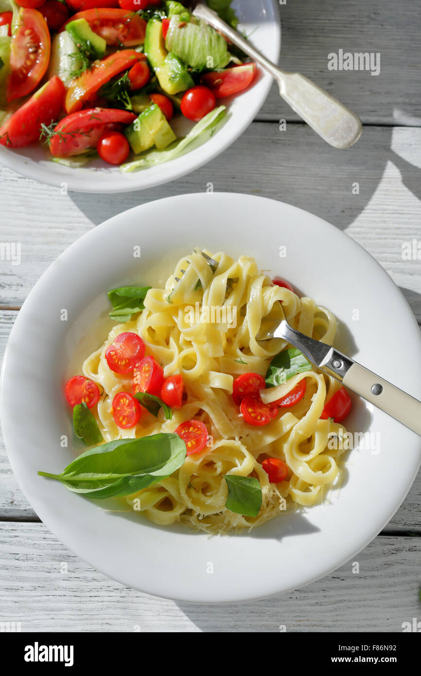 pasta with cherry tomatoes and cheese on white plate - Stock Image