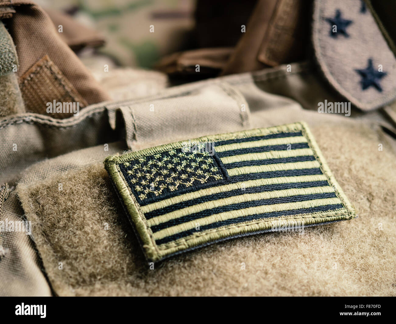 Green US flag patch on the tactical bulletproof vest, selective focus - Stock Image