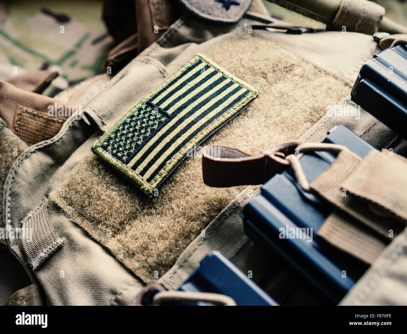 Green US flag patch on the tactical bulletproof vest with M4 magazines, selective focus - Stock Image