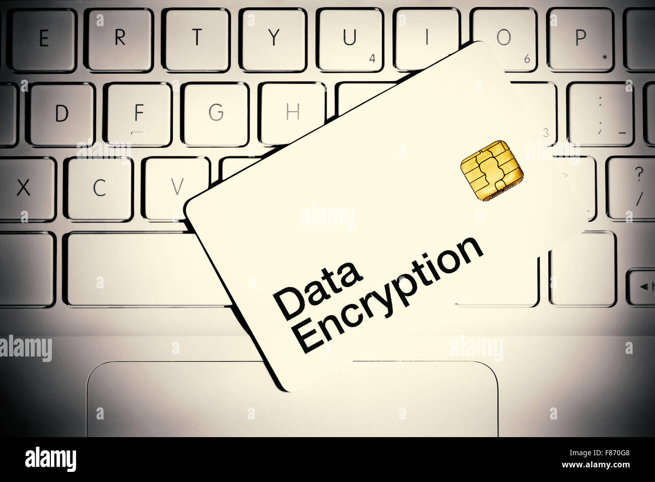 Data Encryption concept. Smart card on a keyboard of white laptop computer. - Stock Image