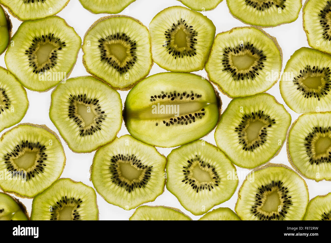 exotic kiwi fruit backlit in studio cut cross and longitudinal sections showing internal seed distribution around Stock Photo