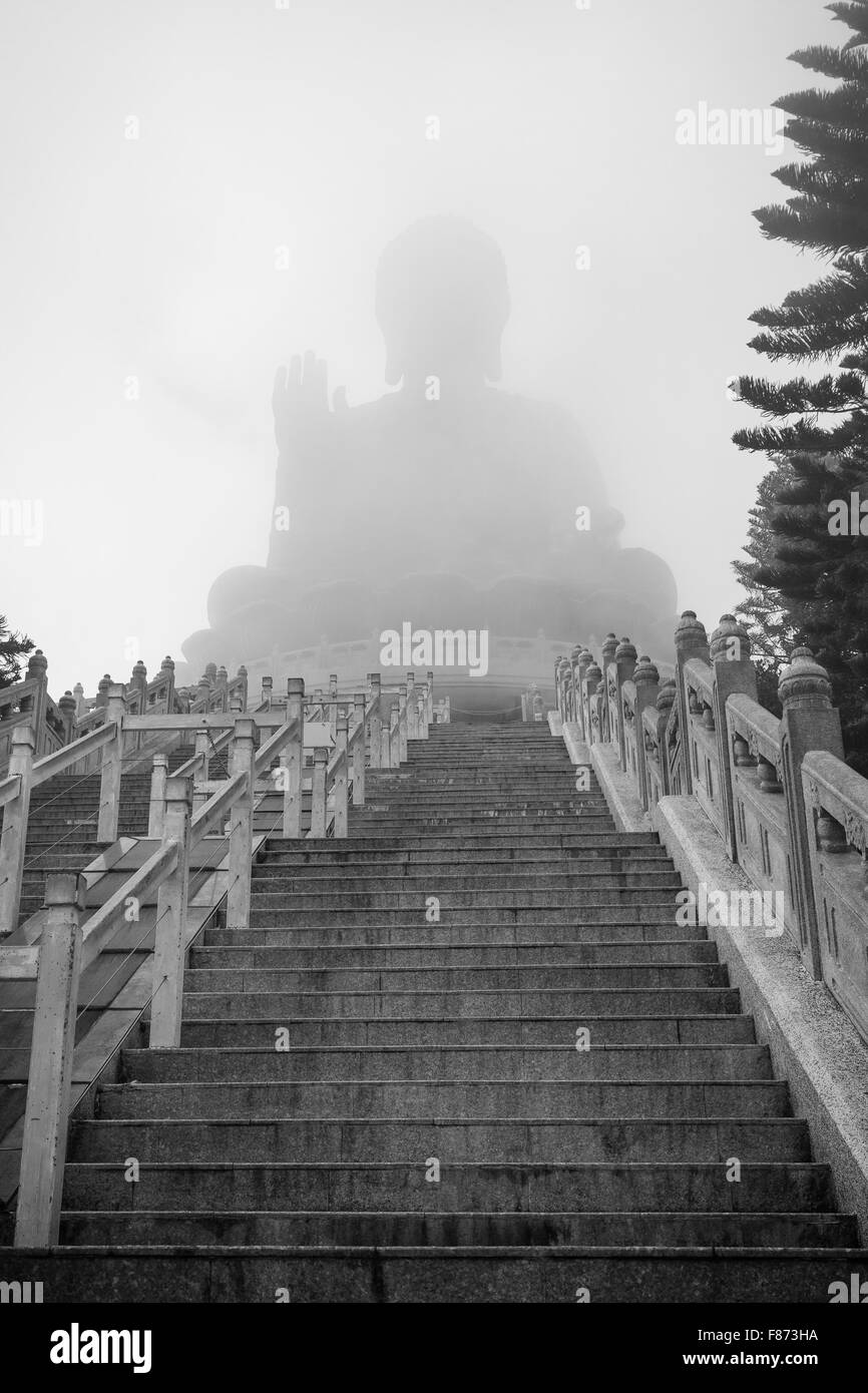 Empty stairs to the foggy Tian Tan Buddha or Big Buddha statue in Lantau Island, Hong Kong, China. Viewed from below. - Stock Image
