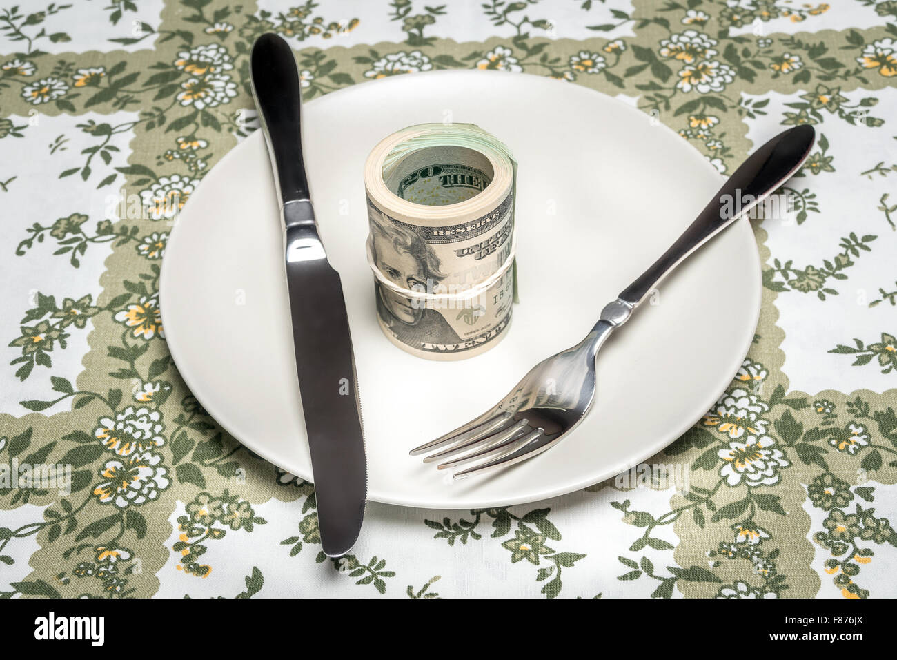 Wad of american dollars served on plate with fork and knife placed on table - business concept - Stock Image