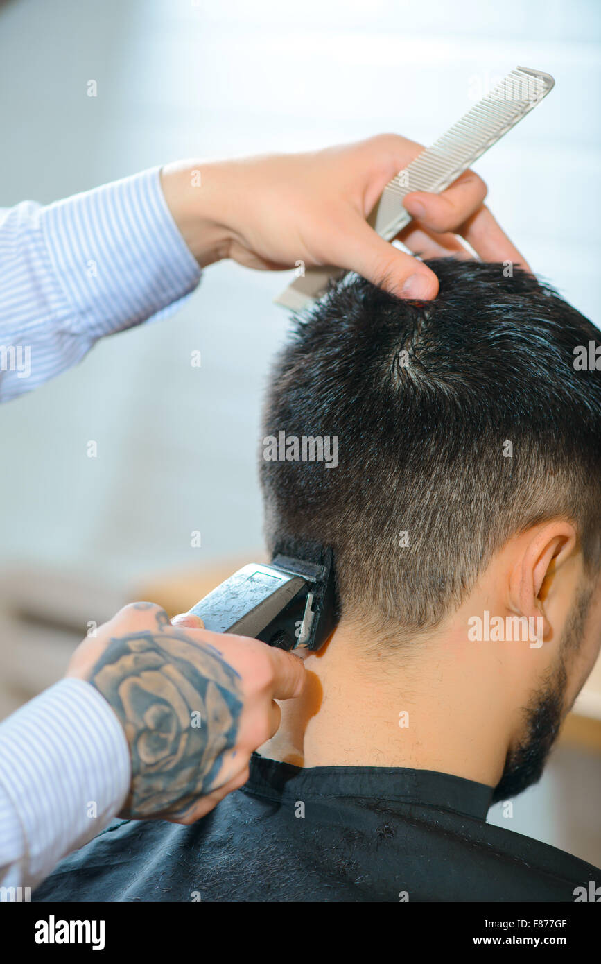 Professional barber making haircut - Stock Image