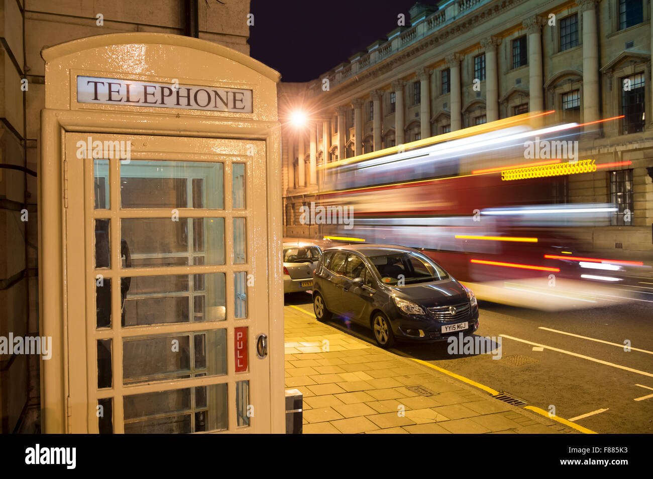 A cream KC Telephone box lit up at night in Hull, East Yorkshire. - Stock Image